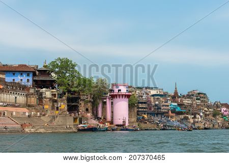 VARANASI INDIA - MARCH 14 2016: Wide angle picture of riverbank with Manikarnika Ghat in Ganges River during day time in Varanasi India.