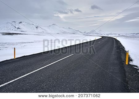 Driveway with orange roadside pillars between the snow fields and snow mountains on the background of the cloudy sky in Iceland. Horizontal.
