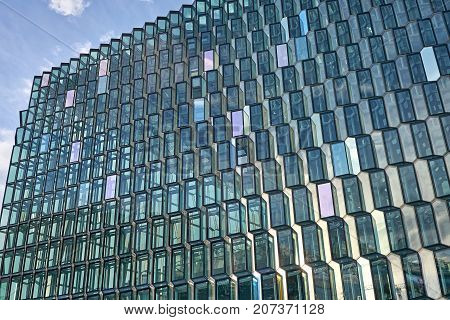 Incredible patterned glass wall of Harpa Hall on blue sky background in Reykjavik in Iceland. Sun shines onto it. Horizontal.