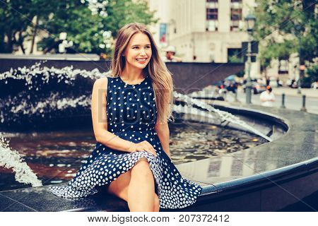 Beautiful young smiling woman sitting on city park fountain at summer day wearing dress and looking to the side