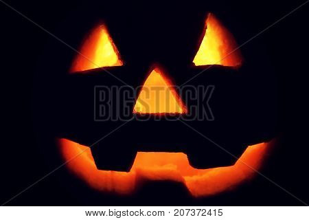 Jack-o'-lantern silhouette on black background. Glowing Jack-o'-lantern pumpkin in dark. Halloween background.