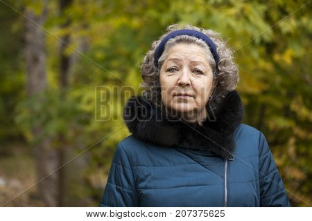 Portrait of a gray-haired elderly woman in an autumn park