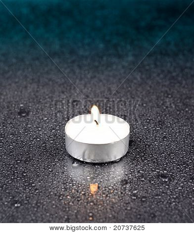 One lit tea Candle on Glass with Drops of Water poster