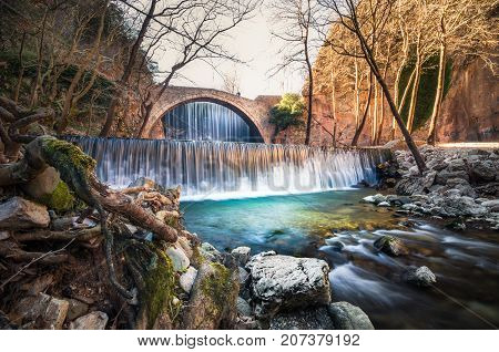 Paleokarya, old, stone, arched bridge, between two waterfalls. Trikala prefecture, Thessaly, Greece