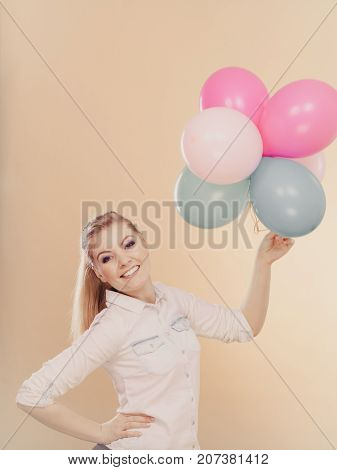Happy joyful girl playing with colorful balloons. Holidays celebration and lifestyle concept. Studio shot on bright