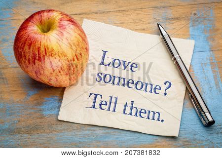 Love someone? Tell them. Handwriting on a napkin with a fresh apple