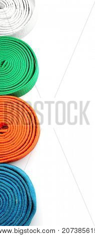 Different colorful karate belts on white background