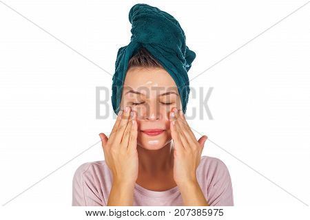 Young woman applying face moisturizer after shower wearing a towel on head - isolated background