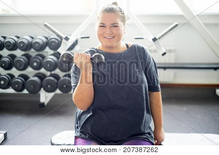 A portrait of a fat girl exercising in a gym
