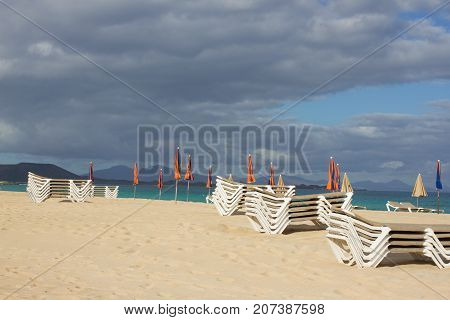 Many beach umbrella and chair on horizon line. Closed parasol on sky background
