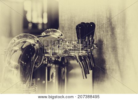 Chromed taps for draft beer in a modern bar. Beer machine detail beer dispenser close-up selective focus retro style black and white