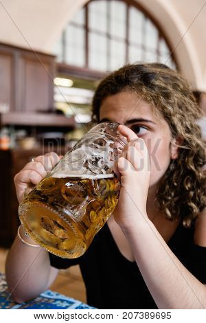 Young adult woman is drinking a big beer jar in resturant with blur background. Concept responsible consumption