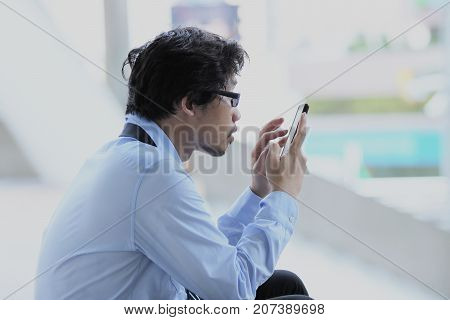 Unemployment concept. Side view of unemployed young Asian man looking mobile smart phone at outside city background.