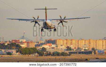 Long shot of propeller plane landing into the airport runway with landing gear