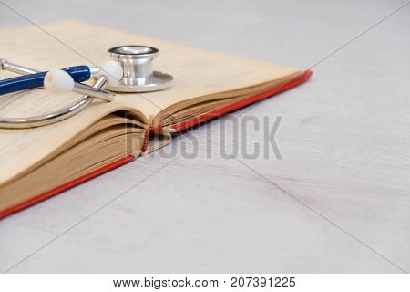 Beautiful Stethoscope Lying On A Reference Books. Stethoscope With Open Book On Wooden Background. M