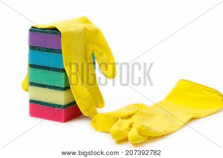a stack of multicolored sponges and yellow rubber gloves for wet cleaning and dish washing on a white background with space for text