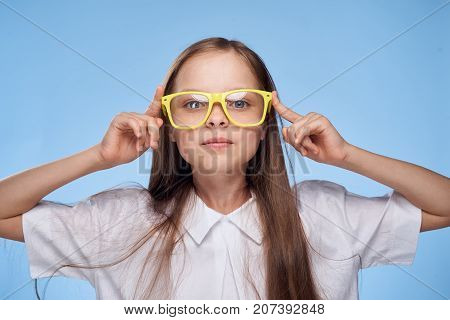 a little girl with long hair in a white shirt and wearing yellow glasses.