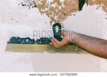 hairy hand guest worker with a steel spatula plastering the wall
