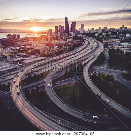 Amazing golden sunset on Pacific Northwest coastal city where Interstate 5 and 90 freeways intersect with skyscraper buildings in downtown city skyline poster