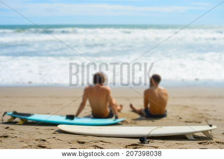 Surfers Rest On The Beach