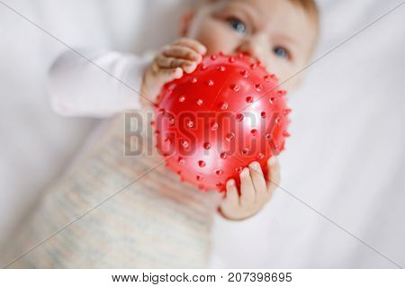 Cute baby playing with red gum ball. New born child, little girl having fun, grabbing and crawling. Family, new life, childhood, beginning concept. Baby learning grab. Selective focus