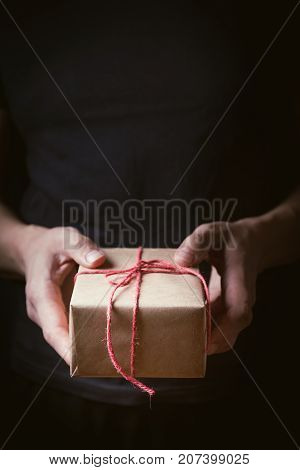 Close up shot of male hands holding a small gift wrapped with red ribbon. Small gift in the hands of a man on black background. Focus on the little box.