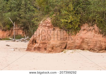 A beautiful seaside landscape with a sandstone caves. Orange sandstone shore at the Baltic sea. Landscape with caves.