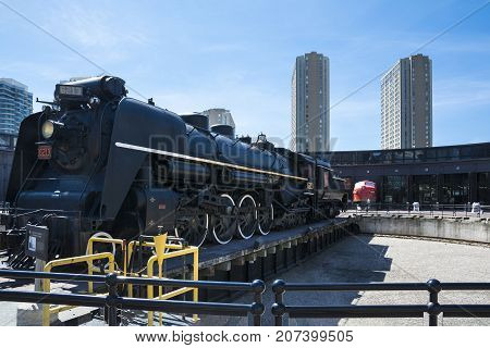 TORONTO,CANADA-AUGUST 2,2015:one of the trains displayed at Toronto's railway heritage center with a view of skyscrapers during a sunny day