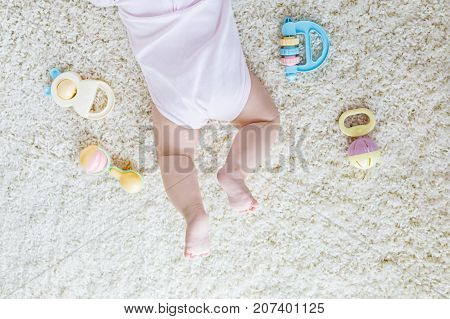 Close-up of baby body and legs with lots of colorful rattle toys. New born child, little girl or boy. Kid having fun. Family, new life, childhood, beginning concept. Closeup for postcard