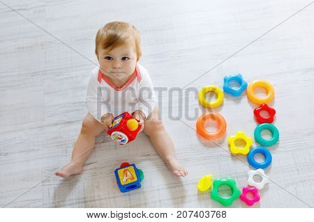 Adorable baby girl playing with educational toys in nursery. Happy healthy child having fun with colorful different toys at home.