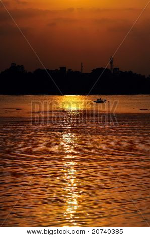 Sunset Country boat heading towards golden rays river ganges poster