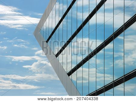 Part of the Dockland office building in Hamburg. The windows of the building reflecting the sky with clouds and creating a surreal view.