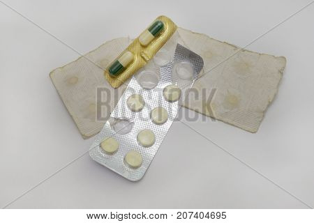 Set Of Old Tablets And Bicolor Capsules In Paper And Plastic Packaging