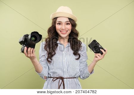 Young asian woman comparing professional and compact camera on green background