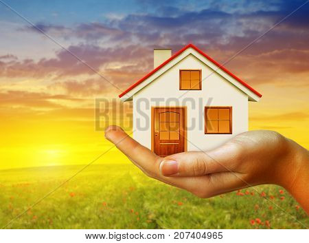 Hand holding small  house at sunset. Real estate and property concept.