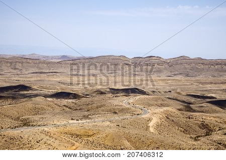 Large crater Ha-Makhtesh Ha-Gadol near Yeruham and the road leading to the colored sands (Israel)