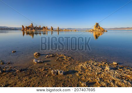 The popular calcareous tufa formation reflects on the smooth waters of Mono Lake, one of the oldest lakes in North America. The Mono Lake Tufa State Natural Reserve, California, United States.