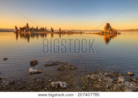 The calcareous tufa formation reflects on the smooth waters of Mono Lake, one of the oldest lakes in North America. The Mono Lake Tufa State Natural Reserve, California, United States. Sunset shot.