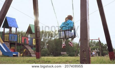 Father pushing child on a swing set. Two girls are swaying opp. each other. Slow Motion