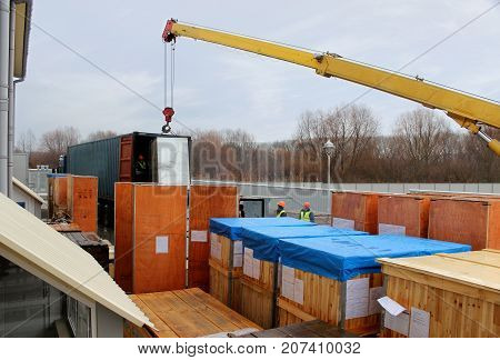 Crane unloading the container from the trailer in the warehouse