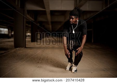 Young afro american man with dreadlocks and dressed in black clothes in the half squat. Full length poster