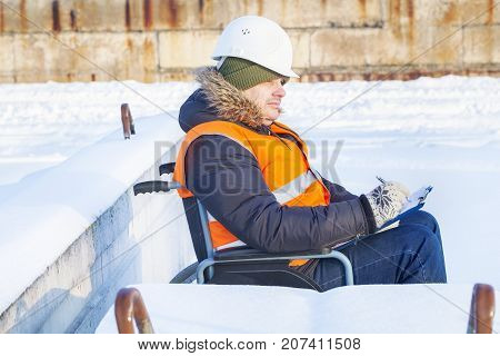 Disabled worker on wheelchair writing in winter day