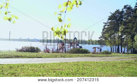 Playground in park near at the lake on sunny weekend day. General video plan.