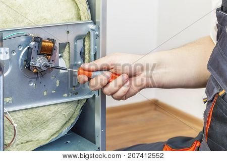 Electrician checking electric cooker in room .