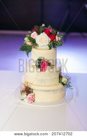 White wedding cake with flowers on table in restaurant. Purple backlight