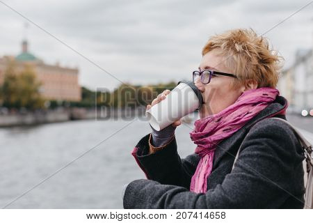 Side view of adult blond woman drinking coffee while standing at water on esplanade.