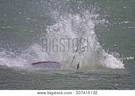 kitesurfer crashing his board in the sea