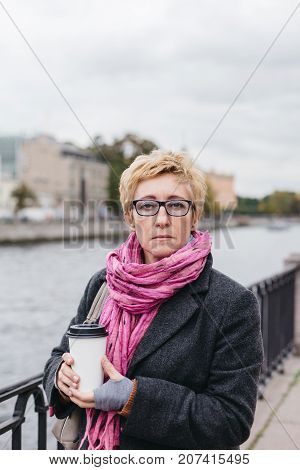 Portrait of adult woman with takeaway coffee cup standing on esplanade.