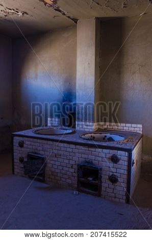 Large oven or stove at ruins of once prosperous German mining town Kolmanskop in the Namib desert near Luderitz, Namibia, Southern Africa.