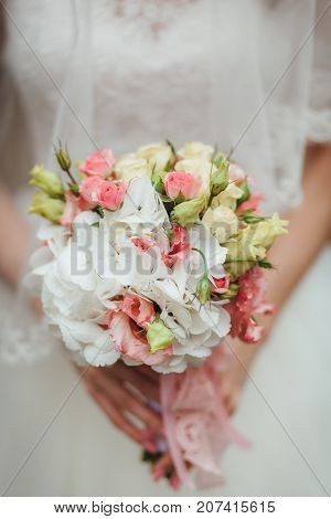 Bride holding big wedding bouquet on wedding ceremony close up shot